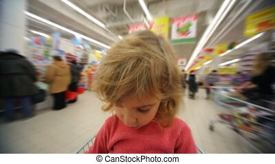 little girl sitting in moving shopping trolley in...