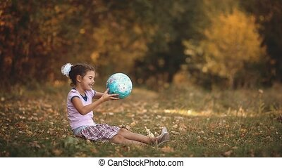 little girl sitting in the autumn forest holding a globe....