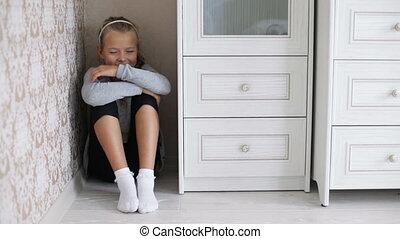 Little girl sitting in the corner of a room refusing doing...