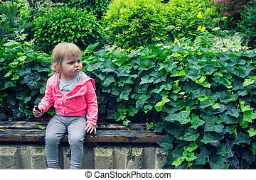Little girl sitting in the garden, sitting on the bench eating candy