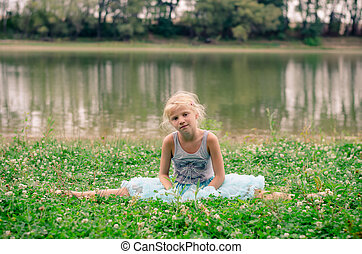 little girl sitting in the grass by the river