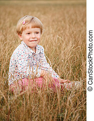 little girl sitting in the grass