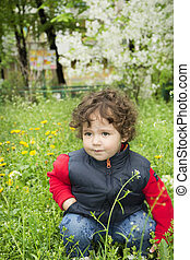 Little girl sitting in the grass near dandelions.