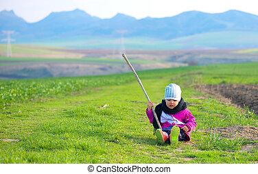little girl sitting in the green field
