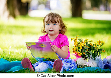 Little girl sitting in the park and reading a book