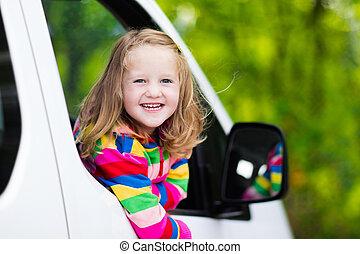 Little girl sitting in white car