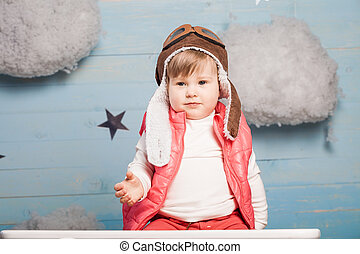 Little girl sitting in wooden toy plane in stylish jacket...