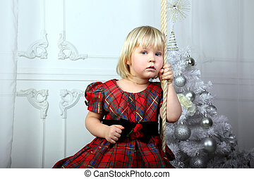 little girl sitting near Christmas tree