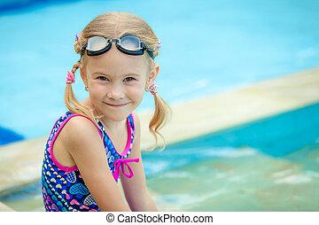 little girl sitting near swimming pool