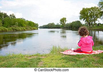 Little girl sitting near the river.