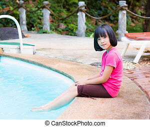 Little girl sitting near the swimming pool