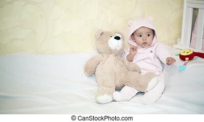 Little girl sitting next to a Teddy bear