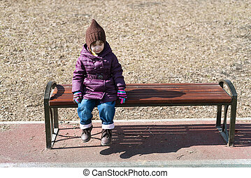 Little girl sitting of a bench