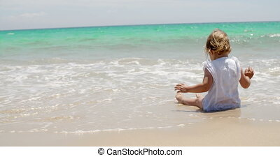 Little girl sitting on a beach close to the water