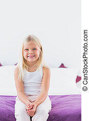 Little girl sitting on a double bed