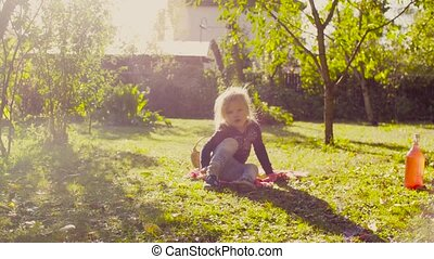 Little girl sitting on a grass in a garden and putting on her shoes