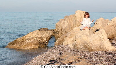 little girl sitting on a rock