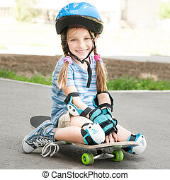 little girl sitting on a skateboard
