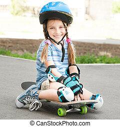 little girl sitting on a skateboard