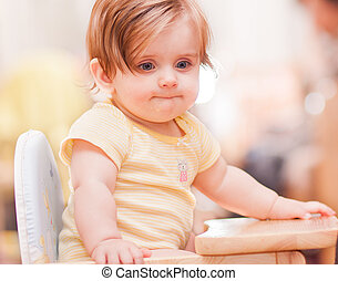 little girl sitting on a wooden chair