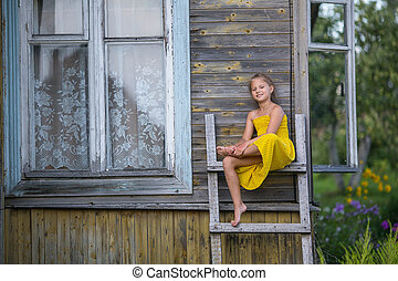Little girl sitting on a wooden