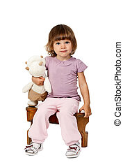 little girl sitting on a wooden stool