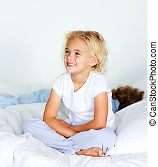 Little girl sitting on bed before sleeping