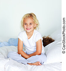Little girl sitting on bed smiling at the camera