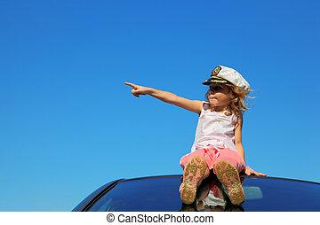 little girl sitting on car roof showing by finger on left side, blue sky