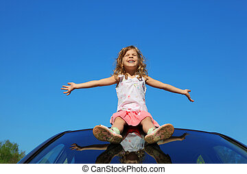 little girl sitting on car roof with open hands on blue sky