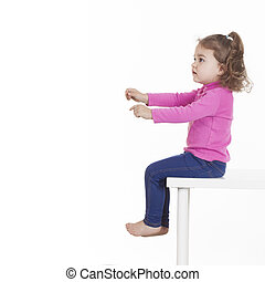 Little girl sitting on chair against of white background