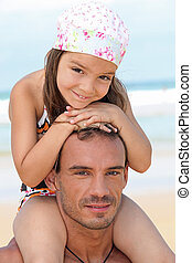 little girl sitting on father's shoulders on the beach