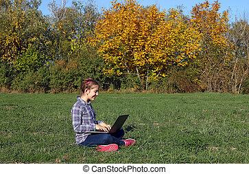little girl sitting on grass and playing laptop autumn season