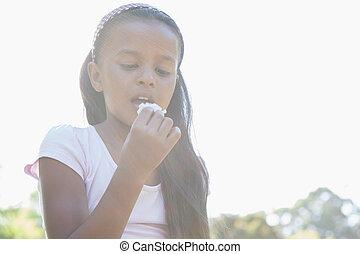 Little girl sitting on grass eating