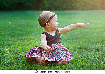 little girl sitting on green grass on the lawn