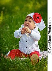 Little girl sitting on green grass