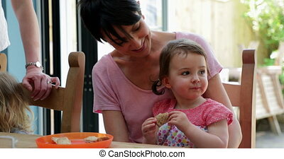 Little Girl Sitting on Her Mothers Lap Trying New Foods -...