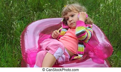 little girl sitting on inflatable armchair andspeaking on...