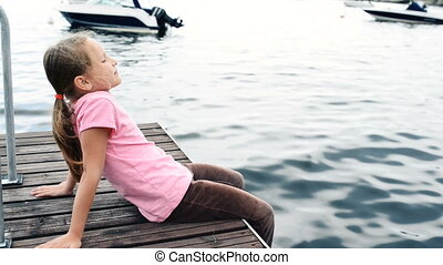 Little girl sitting on private pier enjoying fresh air