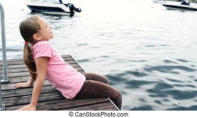 Little girl sitting on private pier enjoying fresh air