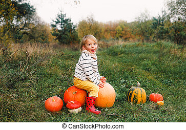 little girl sitting on pumpkins in yellow pants and red boots showing her tongue