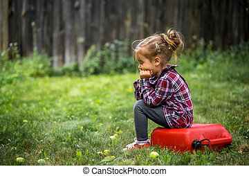 little girl sitting on red canister, a sad emotion - little...