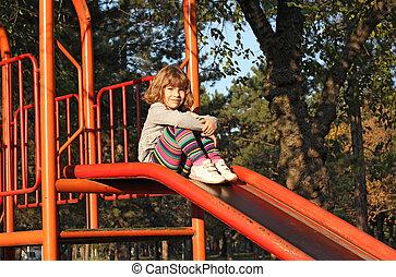 little girl sitting on slide