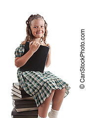 Little girl sitting on stacked books