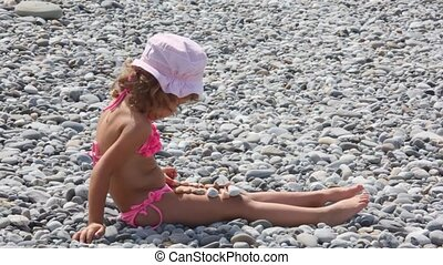 little girl sitting on stones and putting stones on her legs