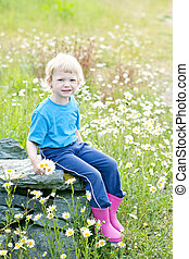 little girl sitting on summer meadow in blossom