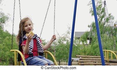 Little girl sitting on swing and eating hamburger on ...