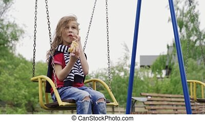 Little girl sitting on swing and eating sandwich on children...