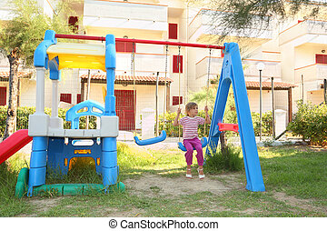little girl sitting on swing at playground and looking at side, sunny day, building