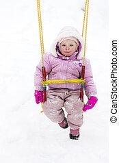 little girl sitting on swing in winter